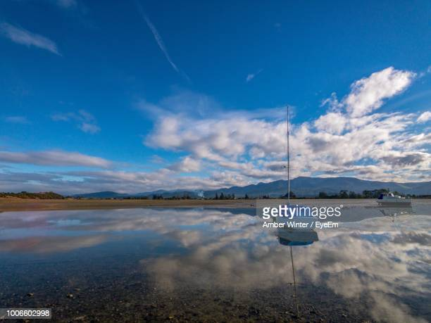 Sailboats Moored In Lake Against Blue Sky
