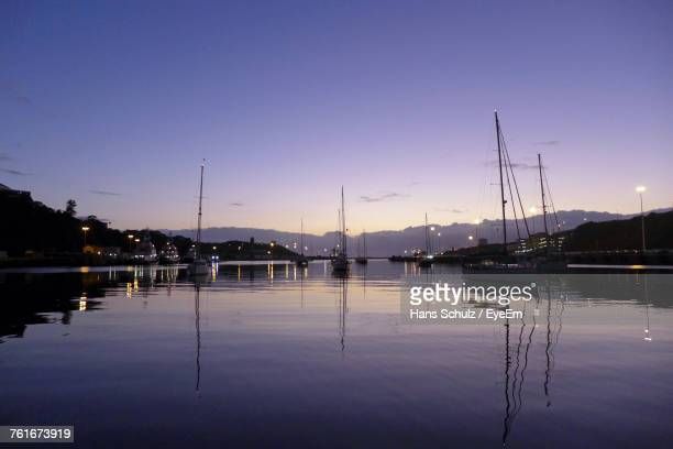Sailboats Moored In Lake Against Clear Sky At Sunset