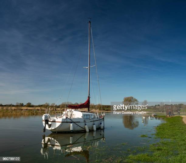 Sailboats Moored In Lake Against Sky