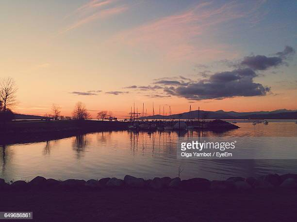 sailboats moored in lake at sunset - english bay stock photos and pictures