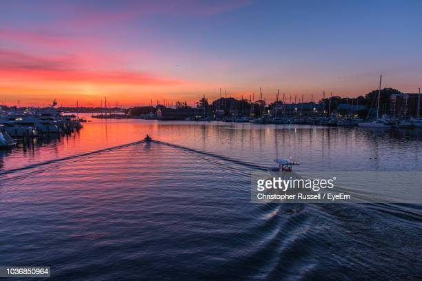 sailboats moored in river against sky during sunset - annapolis stock pictures, royalty-free photos & images
