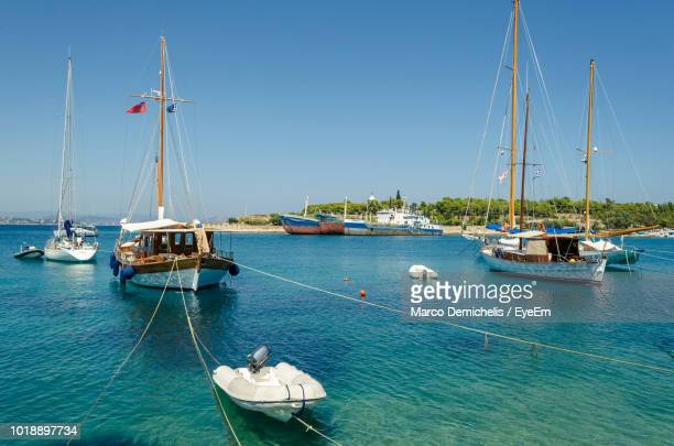 sailboats moored in sea against clear blue sky - spetses stock pictures, royalty-free photos & images
