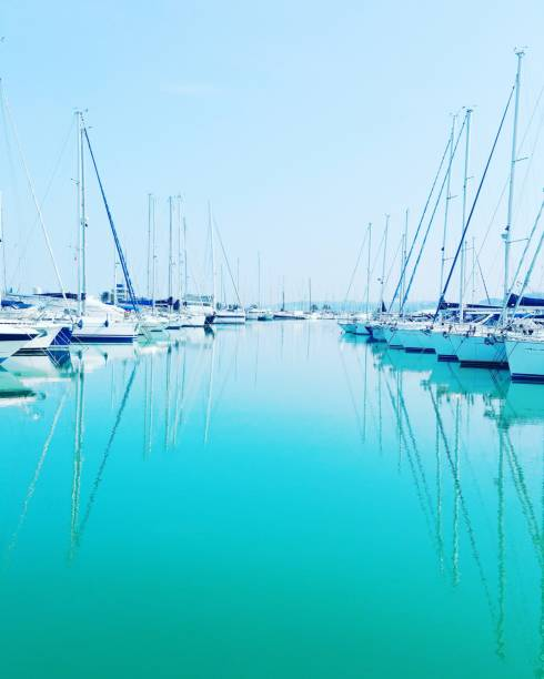 Sailboats Moored In Sea Against Clear Blue Sky