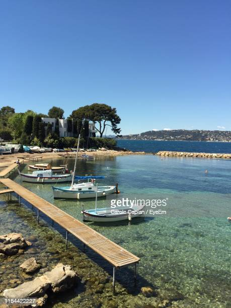 sailboats moored in sea against clear blue sky - antibes stock photos and pictures