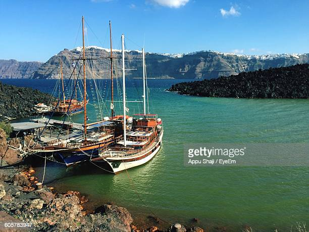 Sailboats Moored In Sea Against Mountains