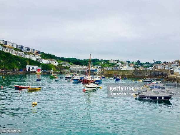sailboats moored in sea against sky - mevagissey stock photos and pictures