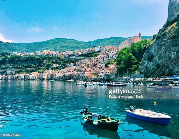 sailboats moored in sea by townscape against sky - calabria stock pictures, royalty-free photos & images