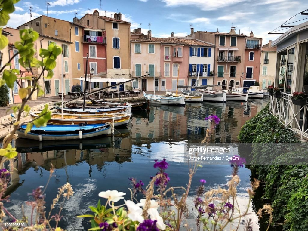 Sailboats Moored On Canal By Buildings In City : Stock Photo