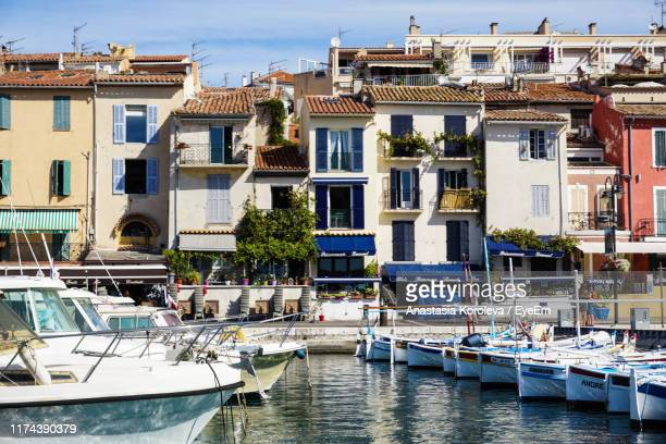 sailboats moored on canal by buildings in city - cassis stock pictures, royalty-free photos & images