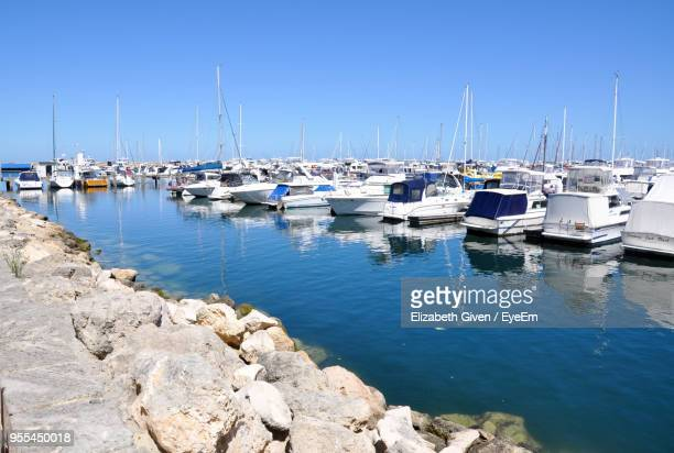 Sailboats Moored On Harbor Against Clear Blue Sky