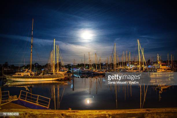 sailboats moored on harbor against sky at night - lymington stock photos and pictures