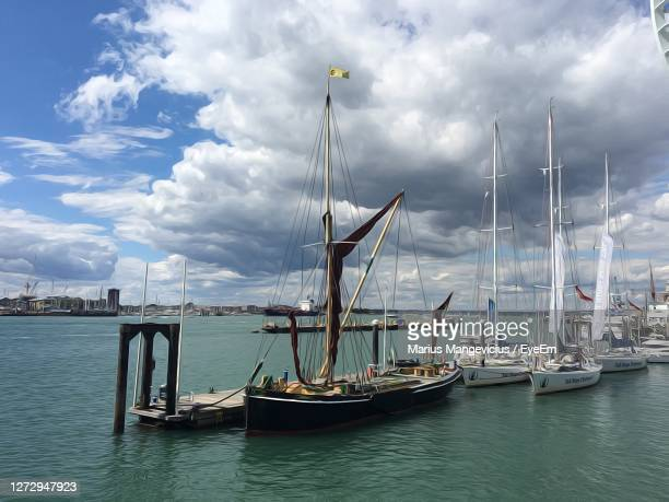 sailboats moored on harbor against sky - 2016 stock pictures, royalty-free photos & images