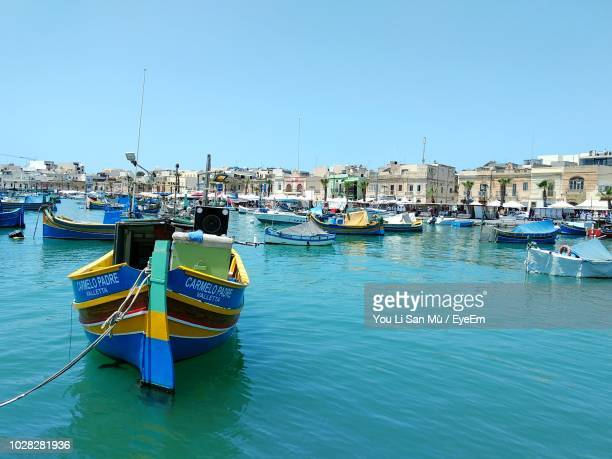 sailboats moored on harbor in city against clear blue sky - marsaxlokk stock pictures, royalty-free photos & images