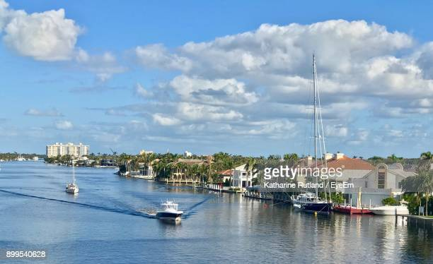 sailboats moored on harbor in city against sky - delray beach stock pictures, royalty-free photos & images