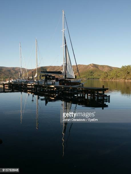 Sailboats Moored On Lake Against Clear Blue Sky