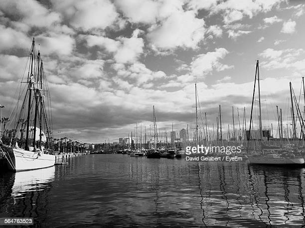 Sailboats Moored On Lake Against Cloudy Sky