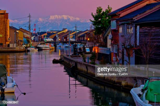 sailboats moored on lake by buildings in city against sky - 富山県 ストックフォトと画像