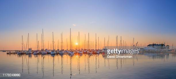 sailboats moored on milwaukee bay against sky during sunset - lake michigan stock pictures, royalty-free photos & images
