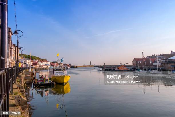 sailboats moored on river by buildings in city against sky - whitby north yorkshire england stock photos and pictures