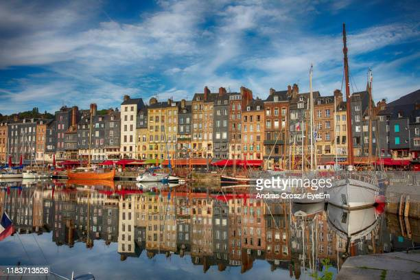 sailboats moored on river by buildings in city against sky - calvados stock pictures, royalty-free photos & images