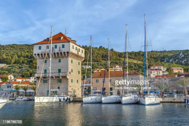 sailboats moored on river by buildings in city against sky - dalmatia region croatia stock pictures, royalty-free photos & images