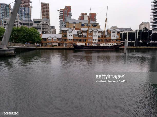 sailboats moored on river by buildings in city against sky - hermes stock pictures, royalty-free photos & images