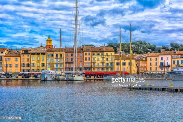 sailboats moored on river by buildings in city against sky - st tropez stock pictures, royalty-free photos & images