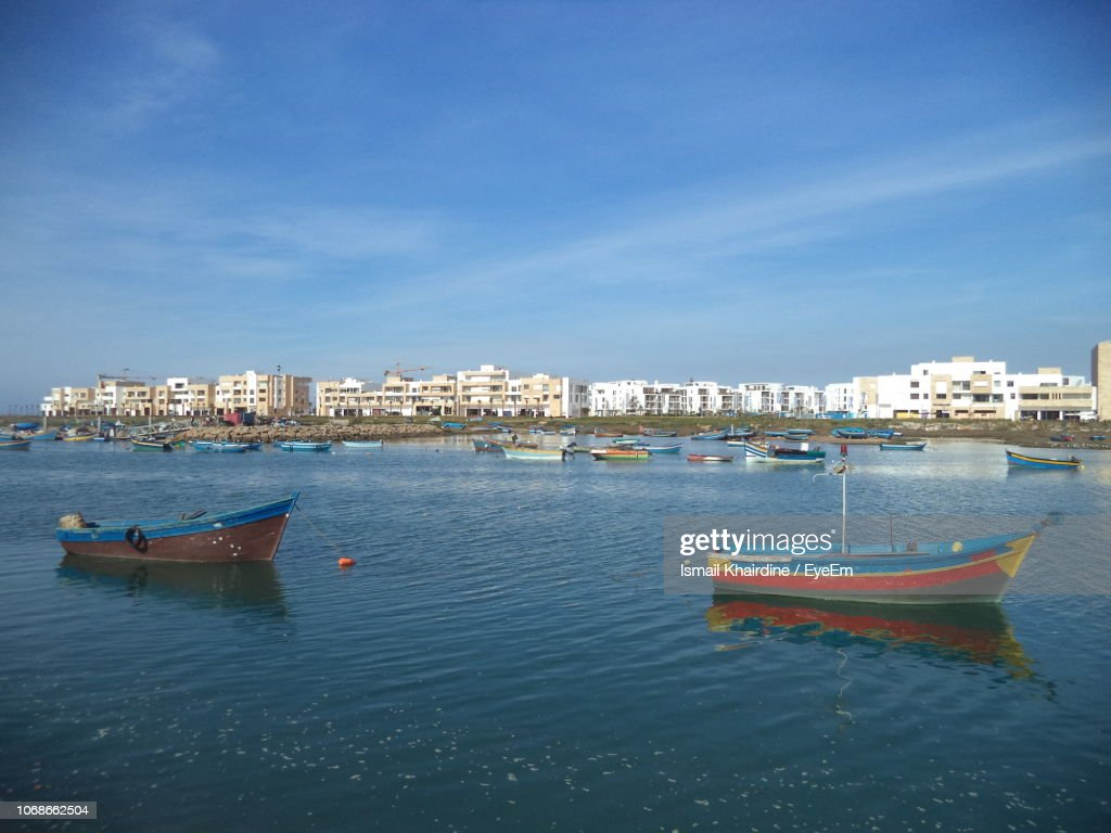 Sailboats Moored On Sea Against Buildings In City : Stock Photo