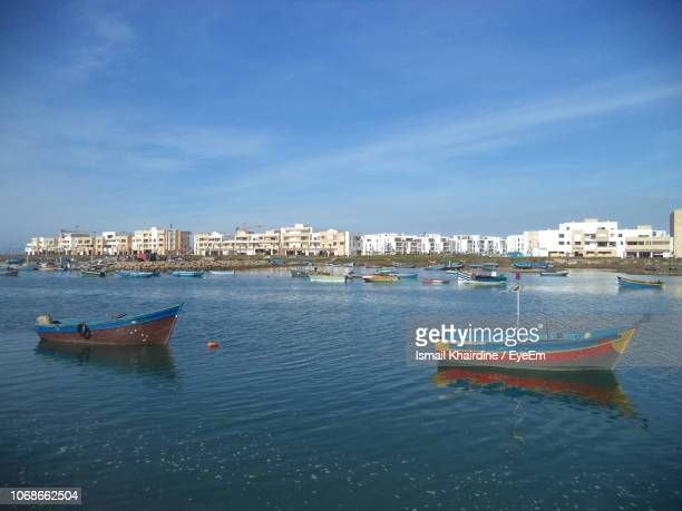 sailboats moored on sea against buildings in city - ismail khairdine stock photos and pictures