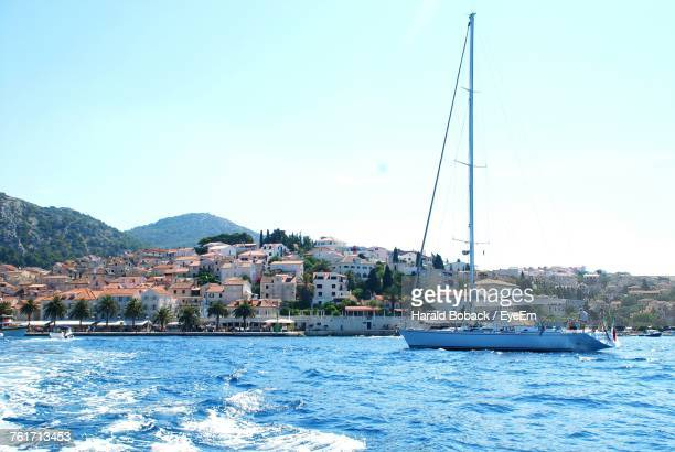 sailboats moored on sea against clear sky - hvar stock photos and pictures