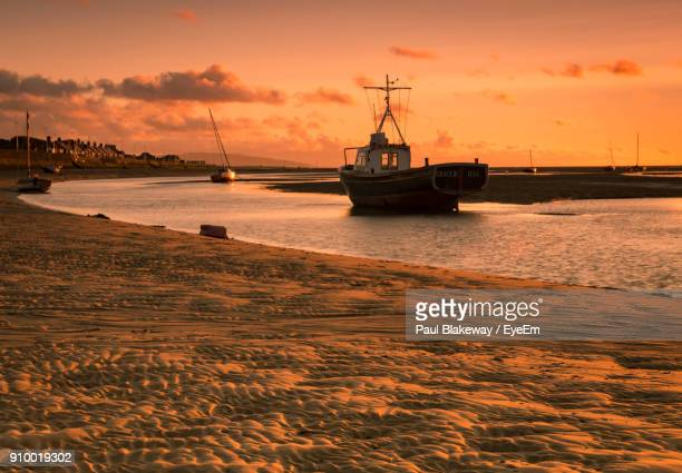 sailboats moored on sea against sky during sunset - birkenhead stock pictures, royalty-free photos & images