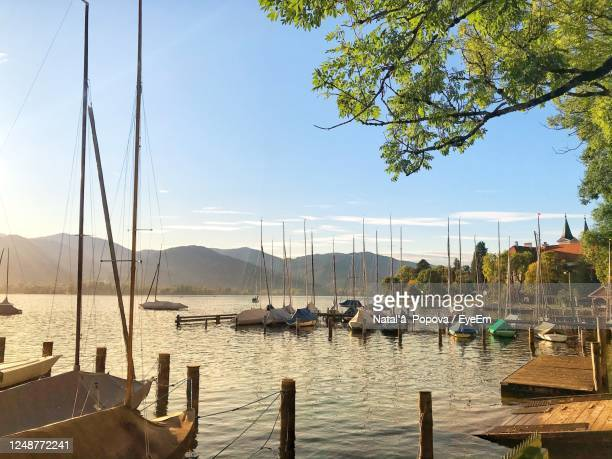 sailboats moored on sea against sky - tegernsee photos et images de collection