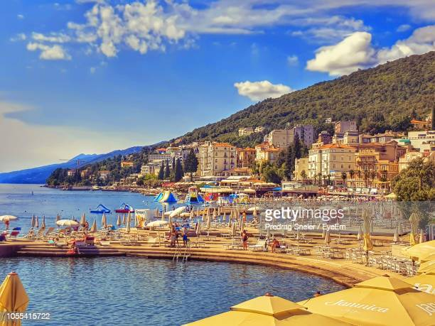 sailboats moored on sea by city against sky - rijeka stock pictures, royalty-free photos & images