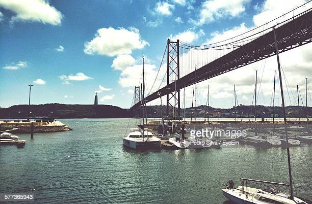 Sailboats Moored On Tejo River By 25 De Abril Bridge Against Sky