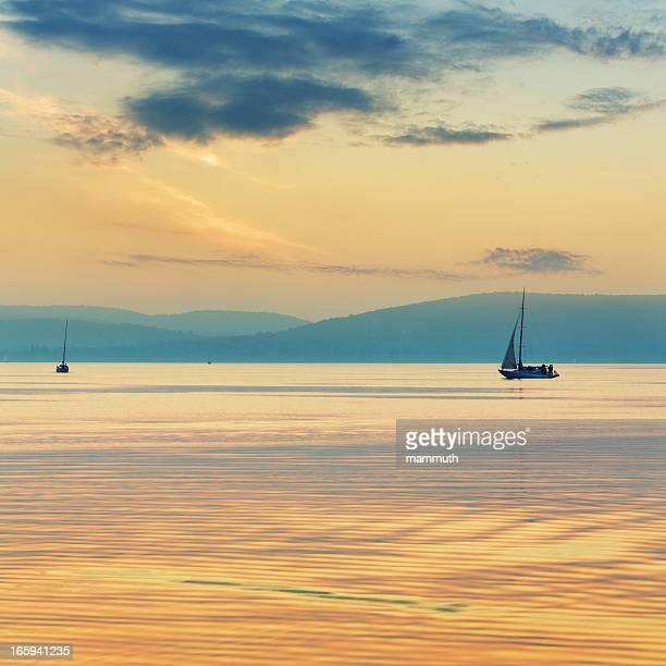 sailboats on the lake at sunset.