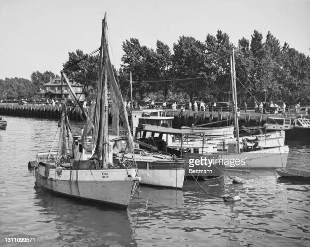 Sailboats on the waters as pedestrians beyond walk along the waterfront of Sheepshead Bay, a neighbourhood in the Brooklyn borough of New York City,...