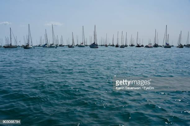 sailboats sailing in lake against sky - lake michigan stock pictures, royalty-free photos & images