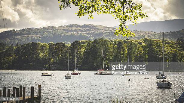 Sailboats Sailing In River By Mountains Against Sky