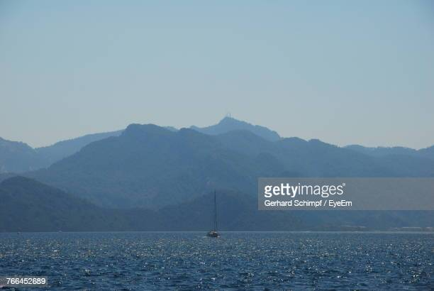 sailboats sailing in sea against mountains - gerhard schimpf stock pictures, royalty-free photos & images