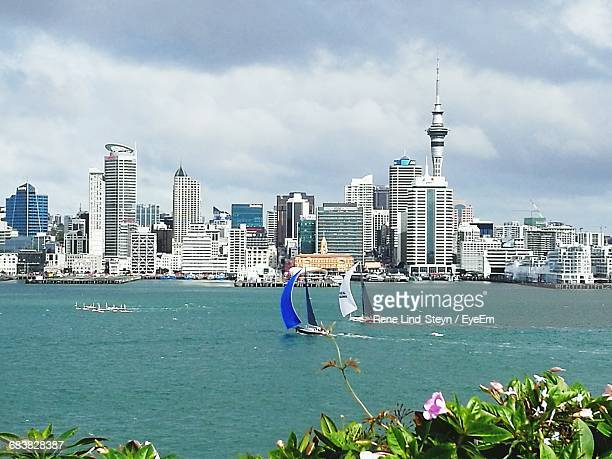 Sailboats Sailing In Sea By Sky Tower Against Cloudy Sky