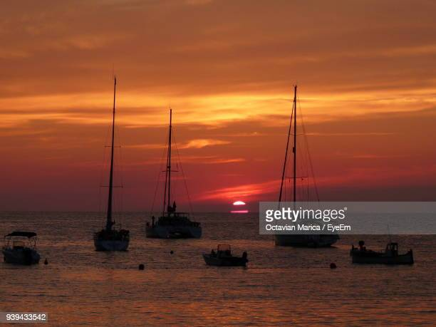sailboats sailing on sea against sky during sunset - marica octavian stock photos and pictures