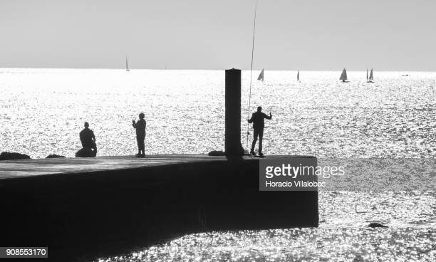 Sailboats tourists and a man fishing seen during a sunny afternoon in Tamariz Beach on January 20 2018 in Estoril Portugal Estoril is an all year...