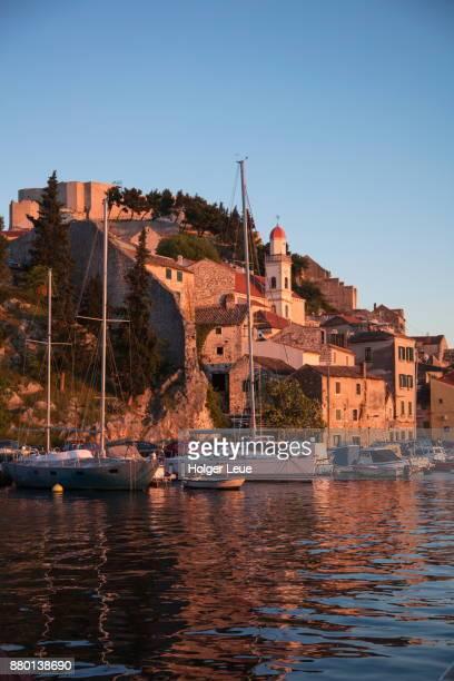 Sailboats, waterfront buildings and St. Michael's Fortress at sunset, Sibenik, Sibenik-Knin, Croatia