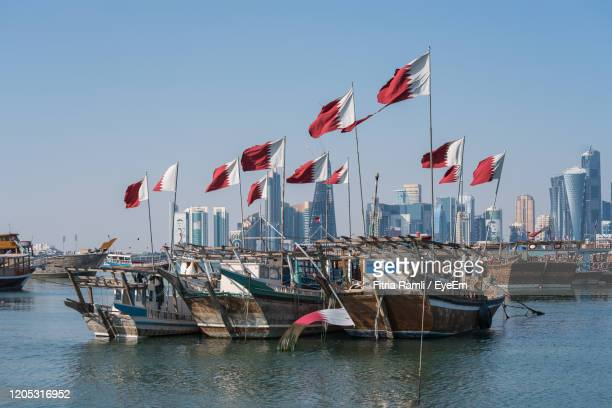 sailboats with qatar flag in city by buildings against clear sky, doha, qatar - qatar stock pictures, royalty-free photos & images