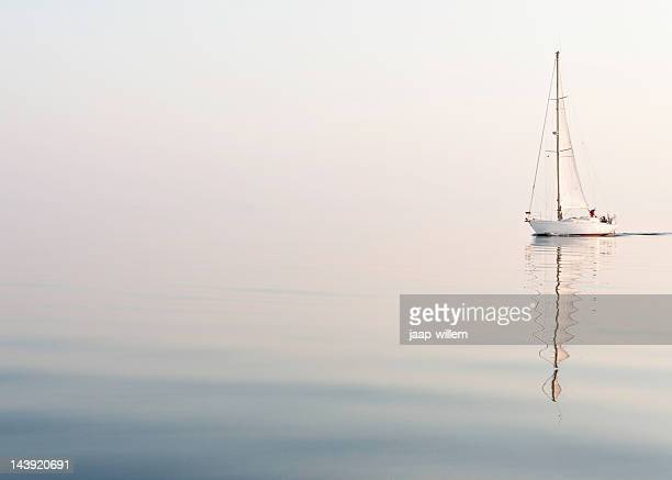 sailing alone at a beautiful foggy sea