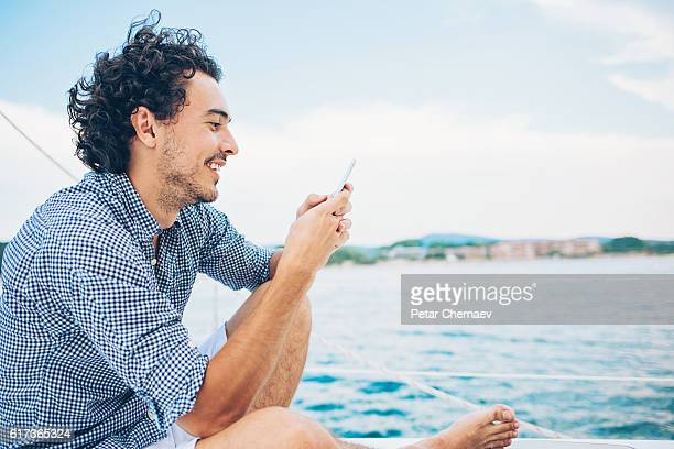 sailing and texting - stereotypically upper class stock pictures, royalty-free photos & images