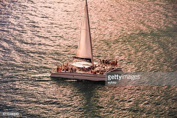 sailing at sunset - catamaran stock photos and pictures
