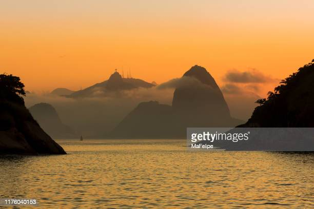 sailing boat entering guanabara bay with sugar loaf mountain and christ the redeemer statue in background. view from piratininga beach in niteroi. - niteroi stock pictures, royalty-free photos & images
