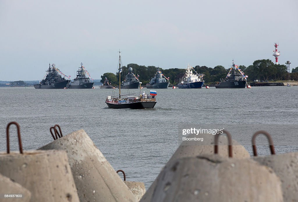 A sailing boat flying a Russian national flag passes warships of the Baltic Fleet at the Vistula lagoon in Baltiysk, Russia, on Sunday, July 31, 2016. Amid Russia's recent rearmament, the Kaliningrad region has increasingly returned to its Soviet-era role as a garrison on the strategic Baltic Sea coast. Photographer: Andrey Rudakov/Bloomberg via Getty Images