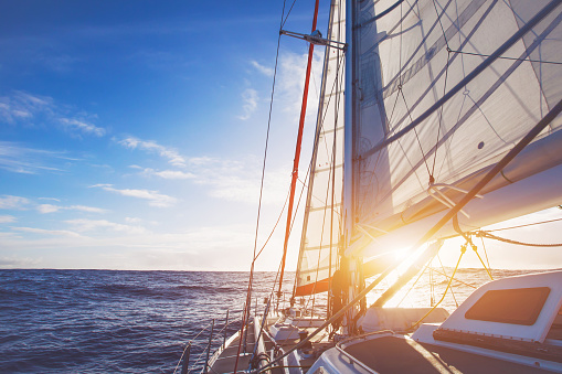 sailing boat in open sea at sunset 1018143468